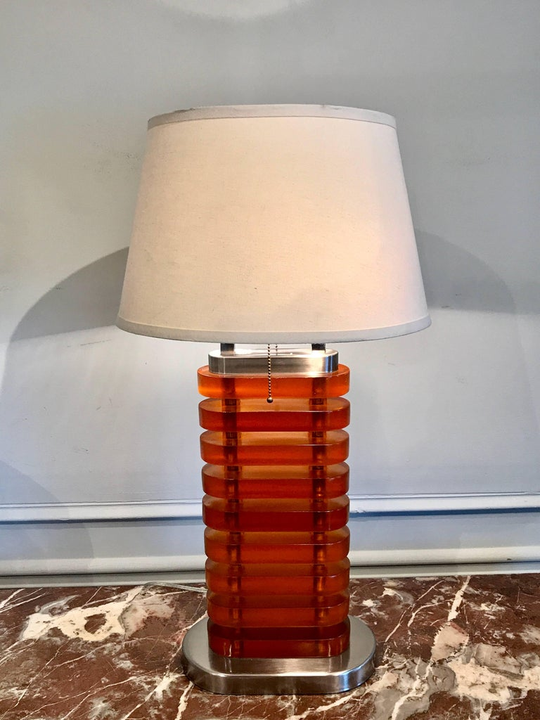Large stacked amber Lucite lamp, consisting of nine thick oval blocks raised on a conforming base. Height of the lamp is 27
