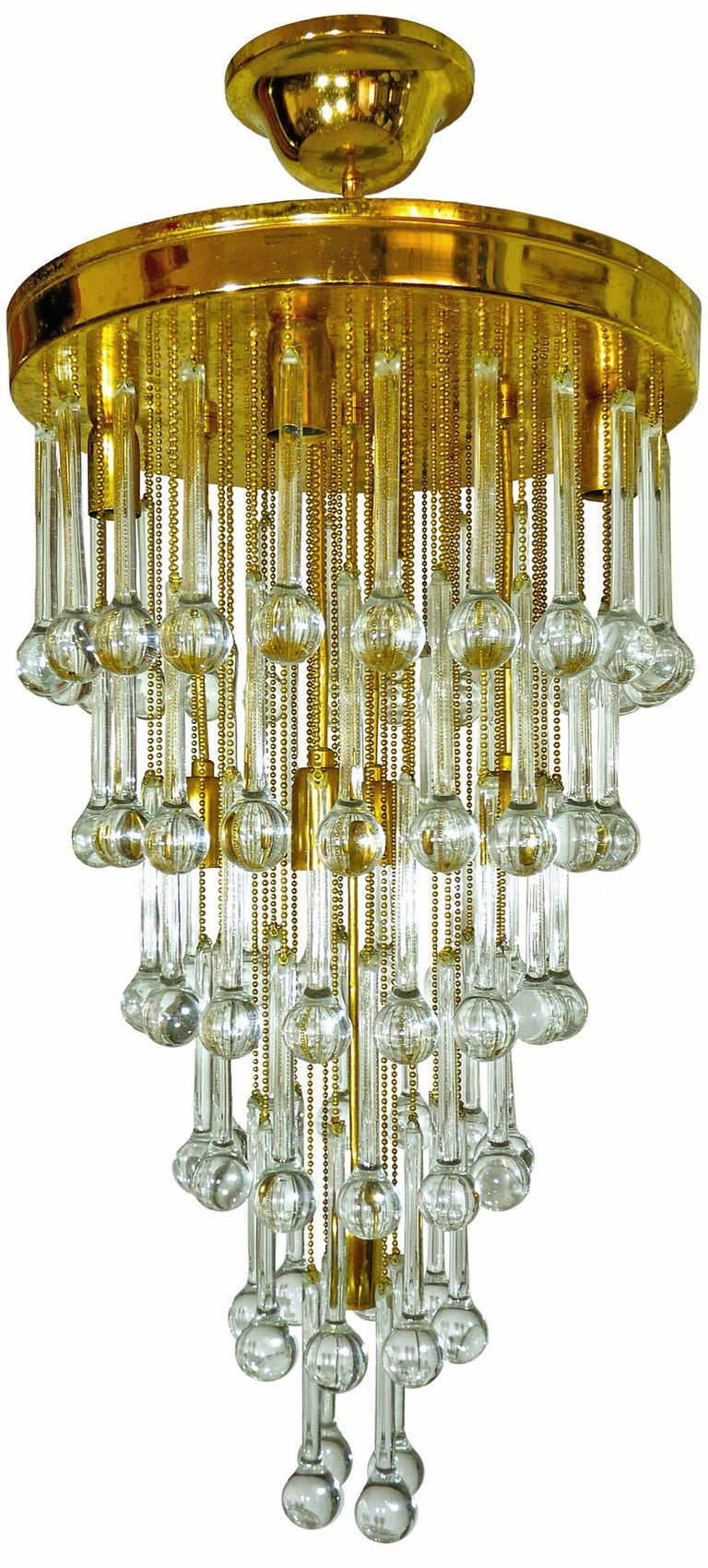 Stunning crystal waterfall wedding cake chandelier with nine-light flush mount chandelier, attributed to Ernst Palme. The piece is gold-plated and detailed with six layers of clear crystal elongated teardrop shaped prisms.