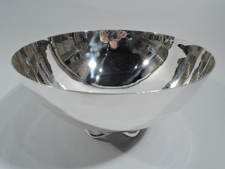 Mid-Century Modern sterling silver bowl. Made by Alfredo Sciarrotta for Cartier in New York. Hemispheric with open base comprising 3 joined c-scrolls. A spare geometric centerpiece. Fully marked including maker's and retailer's stamps, no. 156, and