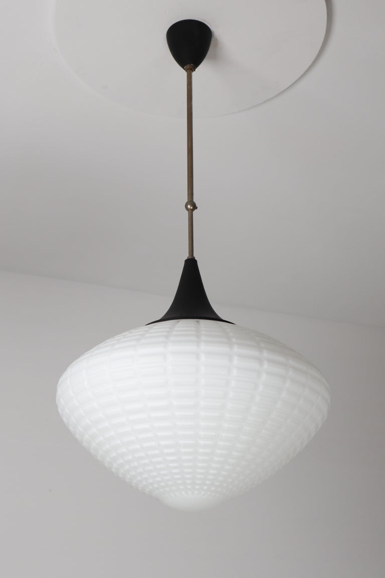 Large midcentury pendant, structured opaline glass, Europe, 1960s. The diffuse light it spreads is very atmospheric. Completed with the opaline glass and metal steel painted canopy on a telescopic rod, these pendants will contribute to a luxurious