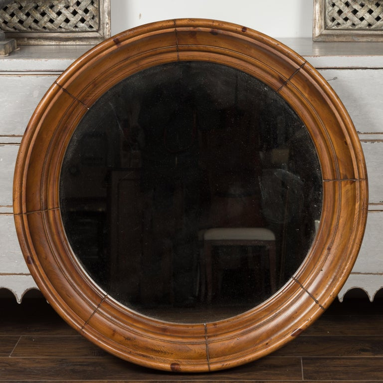 A large vintage American pine bullseye mirror from the mid-20th century, with brown patina and clear mirror plate. Born during the midcentury period, this bullseye mirror features a brown pine molded circular frame surrounding a central flat mirror