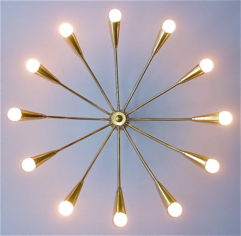 Large midcentury 12-light Sputnik flush mount or ceiling chandelier, Kaiser, Kalmar or Stilnovo style, Germany, circa 1950s. The stylish patinated brass ceiling lamp which is made of high quality has twelve elegant arms for twelve E14 standard screw