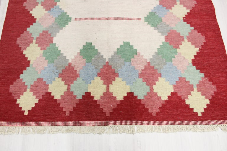 A large Swedish flat weave carpet by unknown designer. The carpet has a red and white base with multicolored geometrical patterns. Very good vintage condition with some smaller stains (should be easily removed when washed).