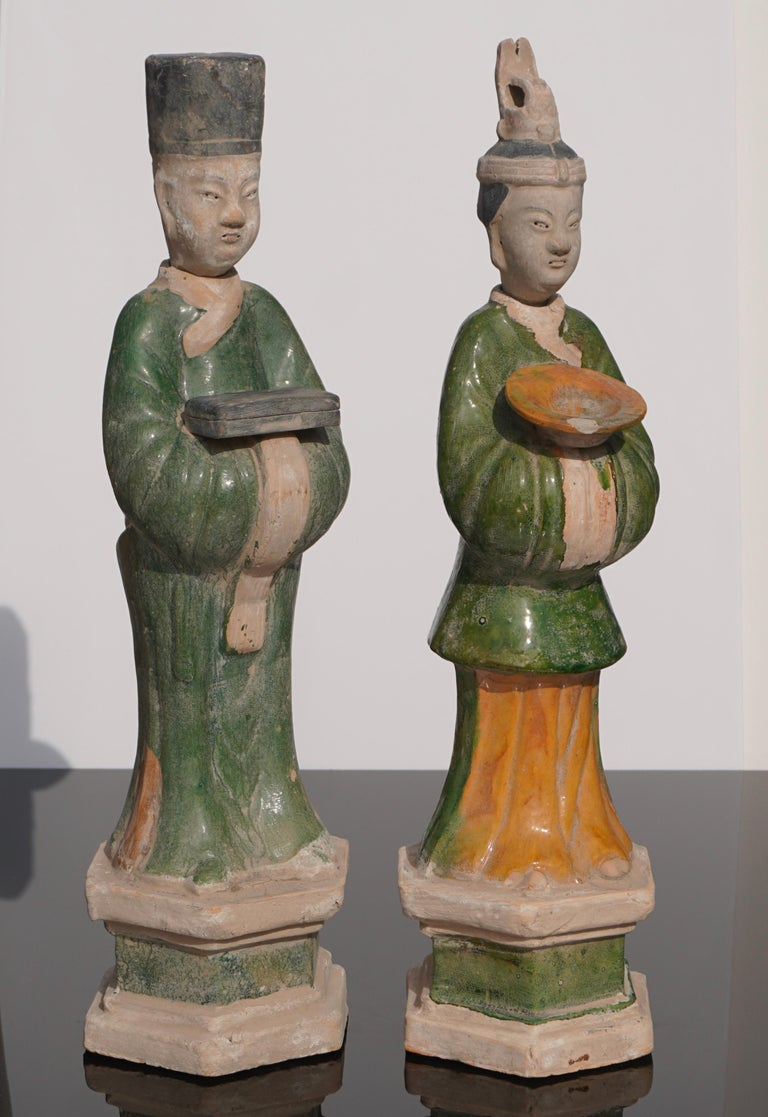 These two Sancai glazed figures in particular are distinguished by their dress, for each wears a unique robe and hat, and by the objects they carry in their arms (one holds a box, the other a bowl). As Chinese statuette art prescribes, the faces are
