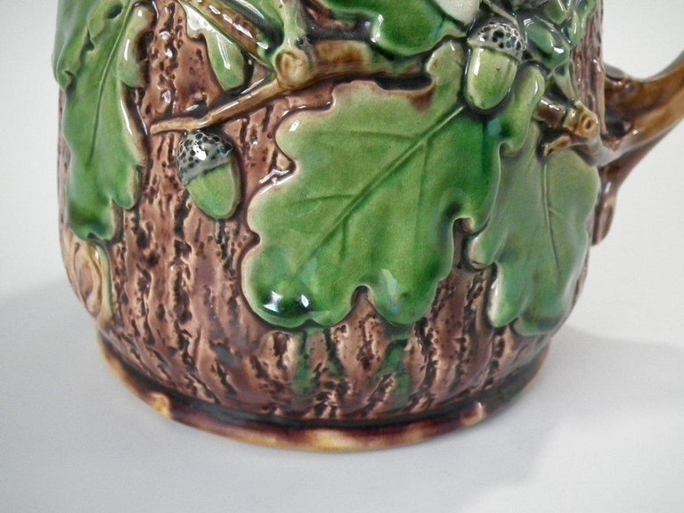 Minton Majolica jug or pitcher which features oak leaves and acorns to the sides and a snail to the handle. Coloration: brown, green, ochre, are predominant. The piece bears maker's marks for the Minton pottery. Bears a pattern number, '6 553'.