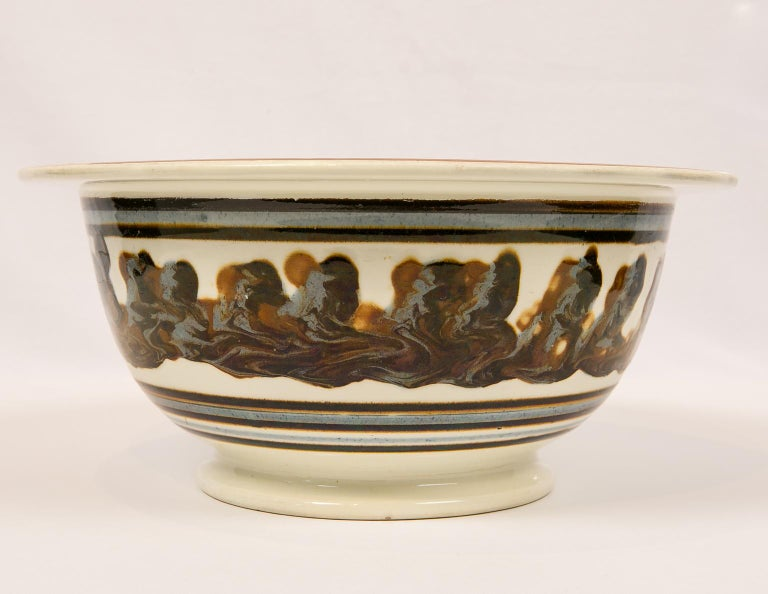 An exceptionally large and rare mid-19th century English mochaware bowl with an everted lip. Made in England circa 1840 the bowl is decorated on the inside with a three color cable of  dark brown, light blue, and light brown. The cable decoration