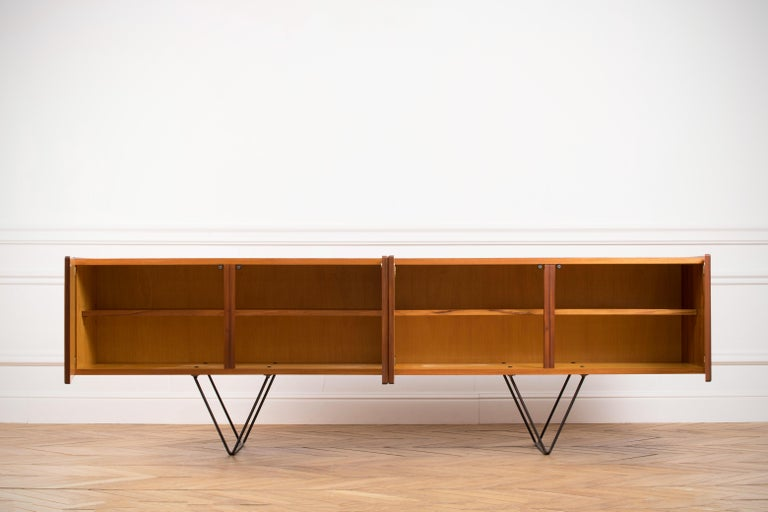 Midcentury teak sideboard from the 1960s. Beautiful minimal legs and carefully hollowed out discreet handles. The storage consists of two large sized cupboards with middle shelves. This classic credenza will enhance the interiors of all styles.
