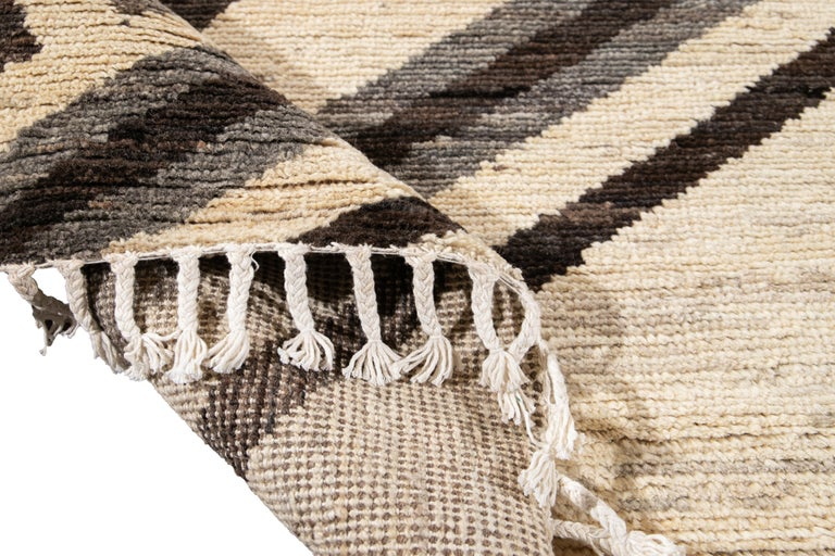 Beautiful oversize Moroccan-style hand knotted wool rug with a beige field. This rug has accents of gray and brown in a gorgeous all-over Geometric tribal design.  This rug measures 12'9