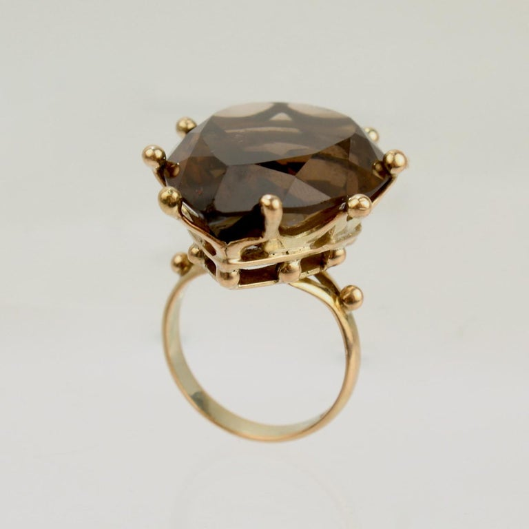 A very fine large modernist 14k gold and smoky quartz cocktail ring.  With a large faceted pear shaped smoky quartz prong set in a 14 karat gold crown undercarriage.  A terrific ring with great scale!  Date: 20th Century  Overall Condition: It is in
