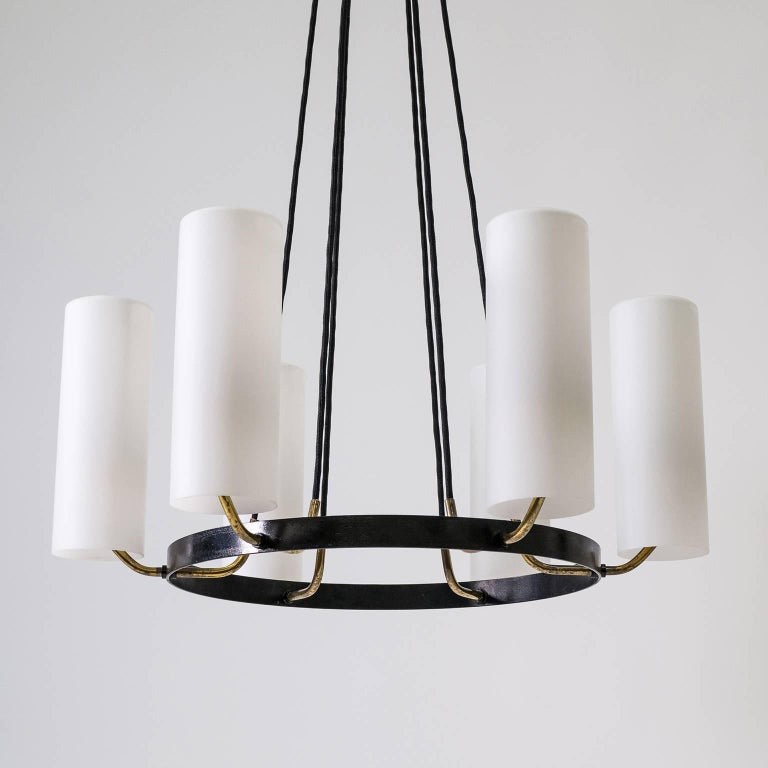 Striking modernist chandelier from the 1950s that exudes a grand presence paired with Minimalist design. Six large cased and satinated glass diffusers appear to be floating atop brass arms attached to a single black lacquered steel ring suspended by