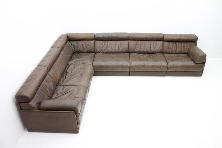 Large living room set in dark brown leather by De Desde Switzerland. Six elements with a high backrest. Ultra comfortable. The elements can also be used as a bed when unfolded. The back is covered with leather and can be placed freely in the