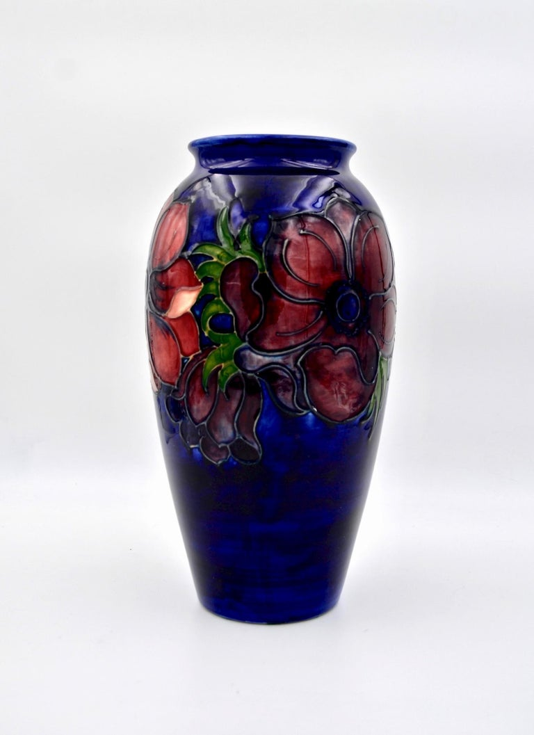 A large Moorcroft art pottery vase made at Stoke-on-Trent, Staffordshire, England and produced in a limited edition. The baluster-shaped vintage vase is decorated in the Anemone pattern featuring colorful tube-lined flowers in shades of maroon,