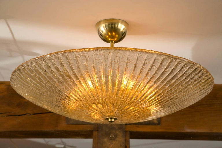 Circular-shaped and reeded Murano blown ceiling fixtures blown in a champagne color with brass fittings.