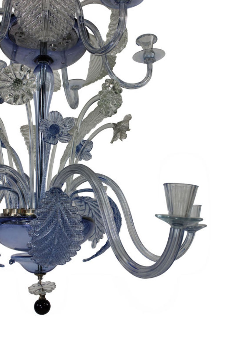 A large Venetian chandelier in pale blue and clear glass. Comprised of twelve arms in two tiers with hand blown stem, arms and foliage. The metal fittings are silver plated throughout.