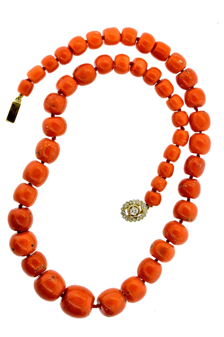 Coral Necklace with 47 natural large coral, ranging in size from 7.7 mm up to 18.2 mm.  This antique necklace, recently restrung, terminates with a diamond and gold clasp.  This necklace is 22.25 inches in length.  The antique clasp has 18 rose and