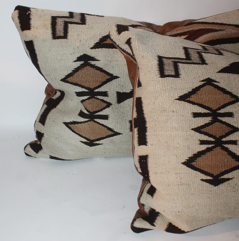 These large Navajo Indian weaving big bolster pillows have leather backings and down and feather fill. The condition is very good.