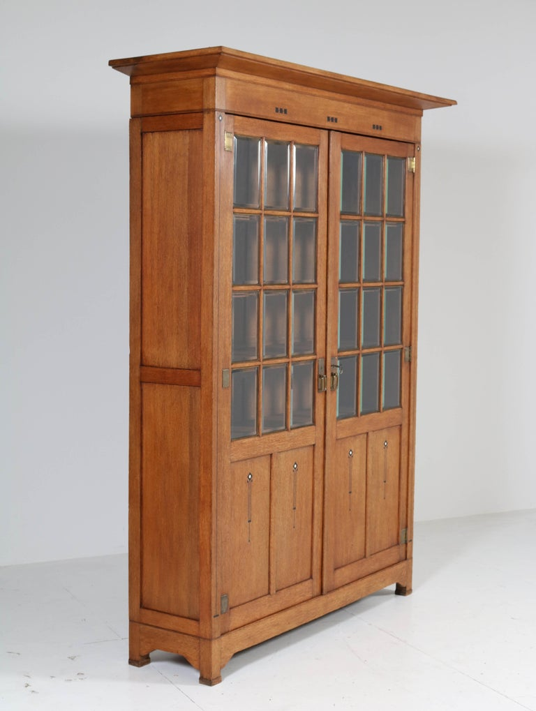 Stunning and rare Arts & Crafts Art Nouveau bookcase. Striking Dutch design from the 1900s. Solid oak with original inlay and original beveled glass. This magnificent piece of furniture can be dismantled for safe transport. Five original wooden