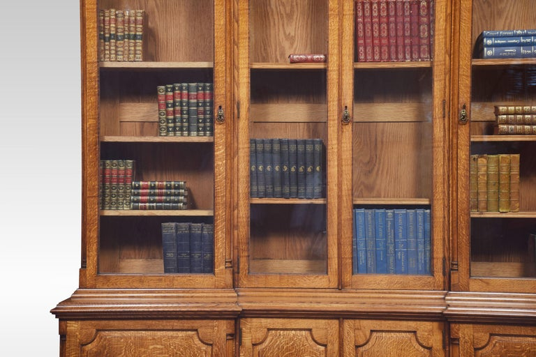 Large oak inverted breakfront bookcase the carved molded cornice above four large glazed doors each section fitted with adjustable shelves. the base section fitted four paneled doors opening to reveal shelved interior all raised up on bracket