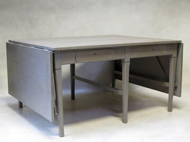 Heavy, solid oak work table, from the French postal service, of efficient, pared-down design. The table has a light-grey, cerused-like finish, and folding extensions on either end. The table has two drawers on one side, and one on the opposite side.