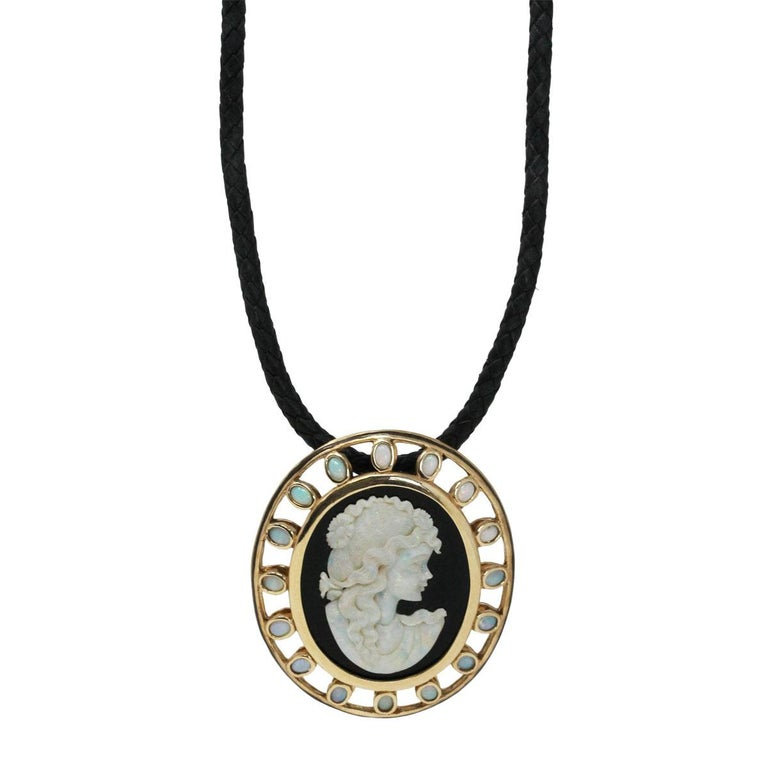 Material: 14k yellow gold Gemstone Details: Black onyx with opal cameo measuring approximately 1.68″ x 1.18″ and bezel set opals measuring approximately 5.40mm x 3.87″ each. Necklace Measurements: Leather cord necklace measures 23″ in length Pendant