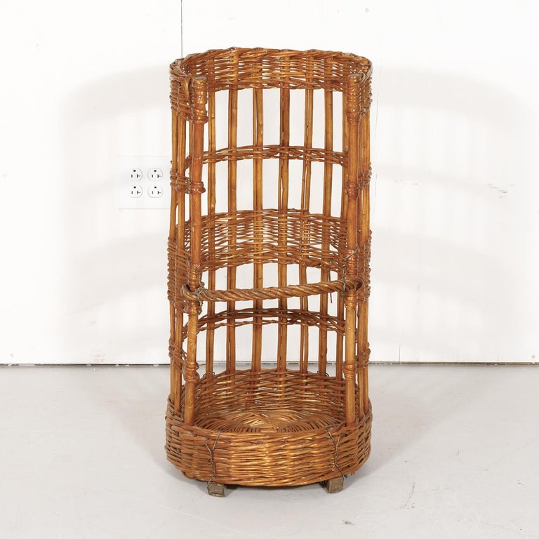 Hard to find open-sided French standing baguette bread basket, circa early 1900s. This semicircle willow basket with a lovely color and aged patina was used to showcase freshly baked baguettes in a French boulangerie. Wooden slat bottom runners for
