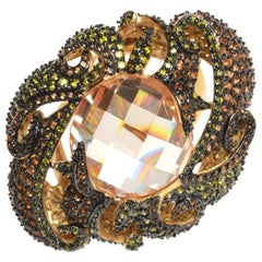 Large orange stone surrounded with yellow, black and orange CZ