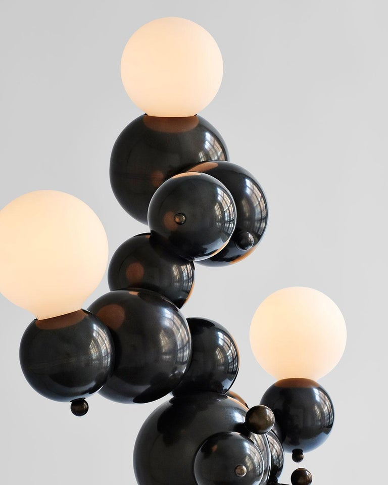 Organic mid-size floor lamp with three lights made of interlocking spun brass spheres, from Rosie Li's