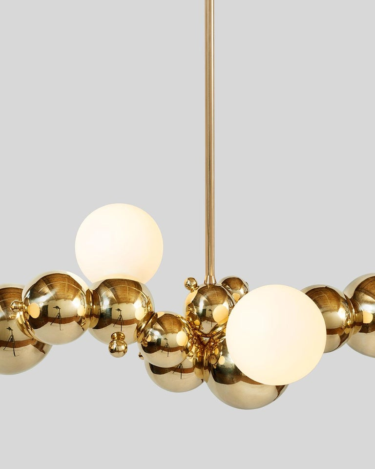Large, organic chandelier with four lights made of interlocking spun brass spheres, from Rosie Li's