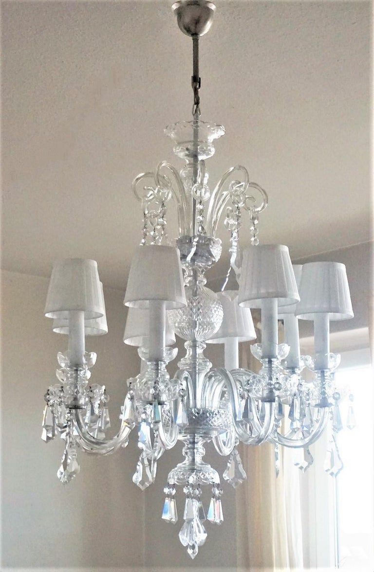 A rare original Venetian handcrafted crystal eight-light chandelier, Italy, 1910-1920. Eight hand blown Murano scroll lamp arms with candelabra light sockets surrounded by glass candle covers. This very elegant chandelier is decorated with eight