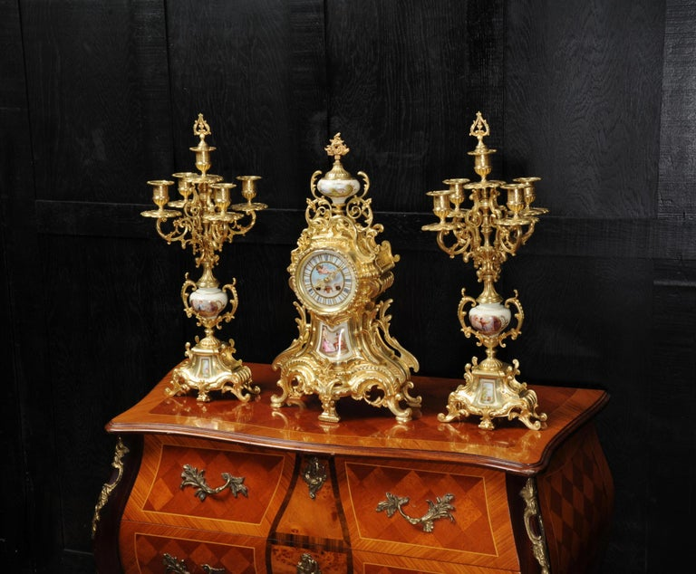A large and beautiful antique French Rococo clock set circa 1900. Beautifully made in finely gilded bronze and mounted with exquisite Sèvres style porcelain. Porcelain has a white ground with panels delicately painted with scenes. The urn shows an