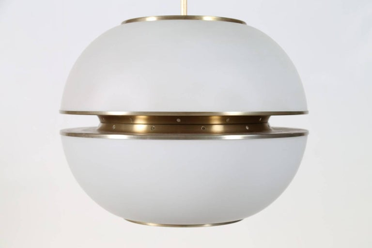Oscar Torlasco (1934-2004)  A large and imposing modernist Lumi chandelier attributed to Oscar Torlasco, in spherical white opaline glass bisected by sleek brass-colored satin finish metal mounts.   Italy, 1960's.  Lumi Milano maker's mark at top of