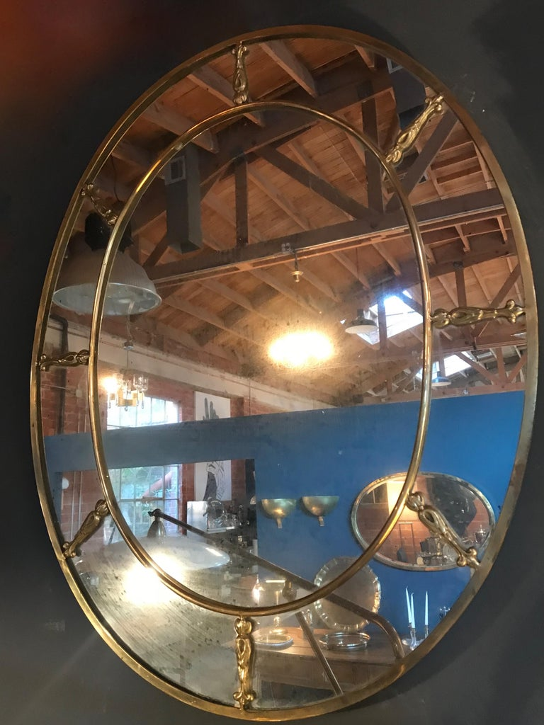 Large oval brass Art Deco mirror from the 1930s. A thick solid brass rim (1.5 inches ) with golden bronze decorative elements applied on the mirror and a continuous brass