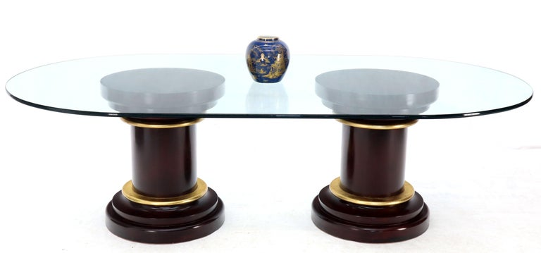 Mid-Century Modern oversized oval glass top dining conference table. Mahogany pedestals bases with gold gilt decorative bezel or trim.
