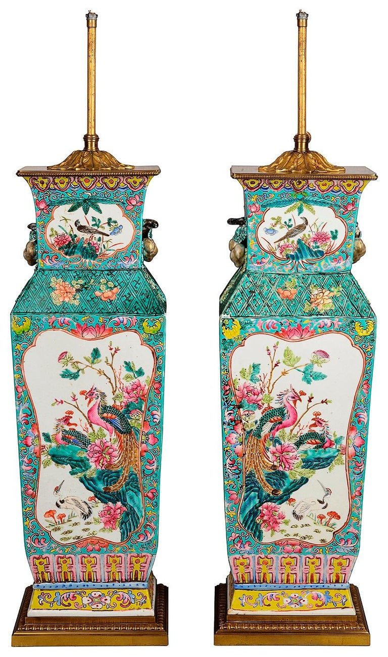 A very good quality pair of Chinese Famille rose vases / lamps. Each with turquoise ground, stylized fruit handles on either side, inset hand painted panels depicting exotic peacocks and ducks among flowers and rocks. Set on gilded ormolu bases and
