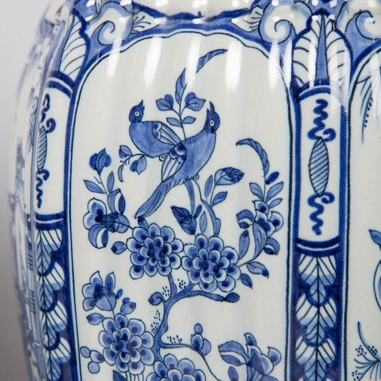 We are pleased to offer this pair of Dutch delft blue and white jars. They are octagonal, fluted. Painted in cobalt blue they are decorated with scenes in panels. The crisp blue decoration creates a distinctive contrast with the underlying white