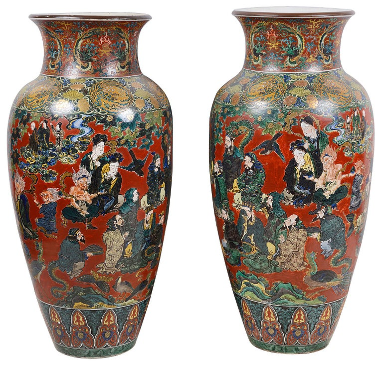 A magnificent pair of Japanese Meiji period (1868-1912) Kutani porcelain vases. Having wonderful hand painted images of attendants gathering in morning, having classical motif decoration top and bottom, signed to bases. Size: 100cm (39.5