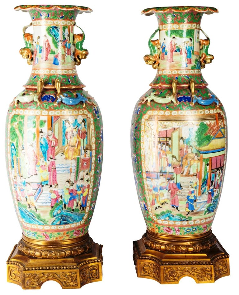 A very impressive pair of 19th century Chinese Cantonese or rose medallion vases or lamps. Each with wonderful bold colors, with classical oriental scenes of courtiers walking around pagoda buildings and gardens. The green ground having beautiful