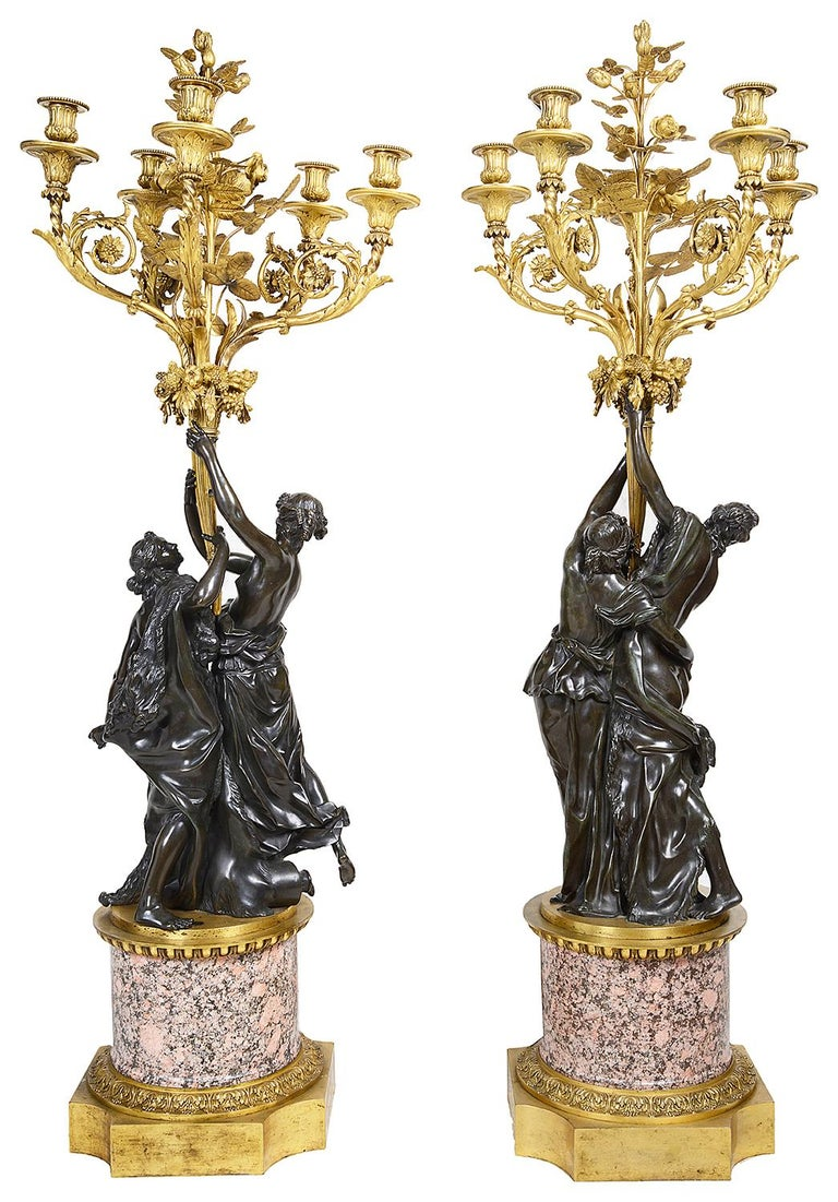 A very impressive good quality pair of 19th century classical bronze and ormolu candelabra, each with ormolu roses, leaves and four scrolling foliate branches, supported by a pair of classical semi nude maidens, raised on gilded ormolu-mounted