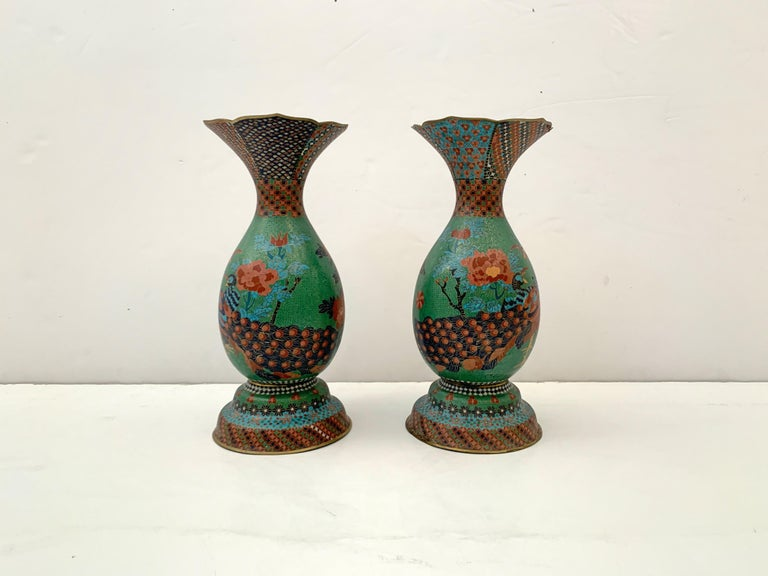 An impressive pair of Japanese cloisonné peacock vases attributed to Kaji Tsunekichi (1803 - 1883), Meiji period, mid-19th century, Japan.   The vases of pear shape, with a high splayed foot and large everted trumpet mouth. The bodies with a