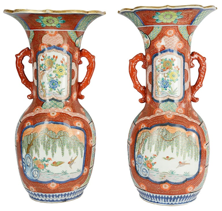 A very decorative and impressive Meiji period (1868-1912) Japanese Kutani flare necked twin handle vases. Each with orange ground feather decoration, inset painted panels with blossom trees, birds and flowers. This pair of vases we can convert to