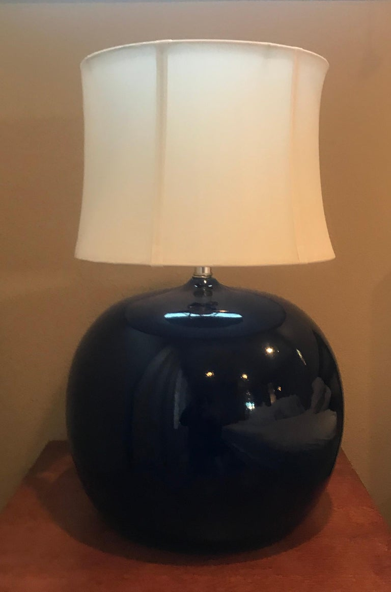 An orb shaped pair of ceramic 1970s Portuguese table lamps in a dark cobalt blue with chrome hardware. Rewired.