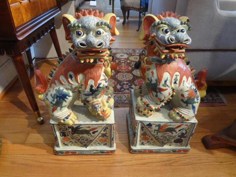 Stunning pair of antique Chinese hand decorated porcelain foo dogs or foo lions. This beautiful pair of Chinese foo dogs are executed in fabulous and unusual colors and date to the 1930s-1940s. They are Artist-signed (see photos).