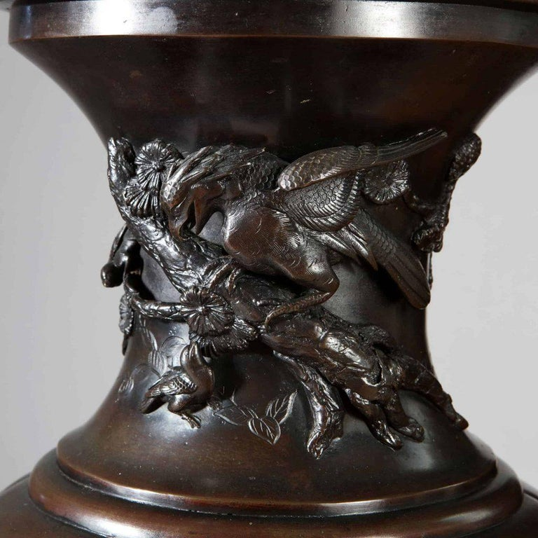 A pair of large Japanese Bronze vases dating from the Meiji period. Of baluster form with raised panels of birds among tree branches foliage and flowers, the main body of the vases with six unique and matching scenes. Japan 1880  Measures: Height