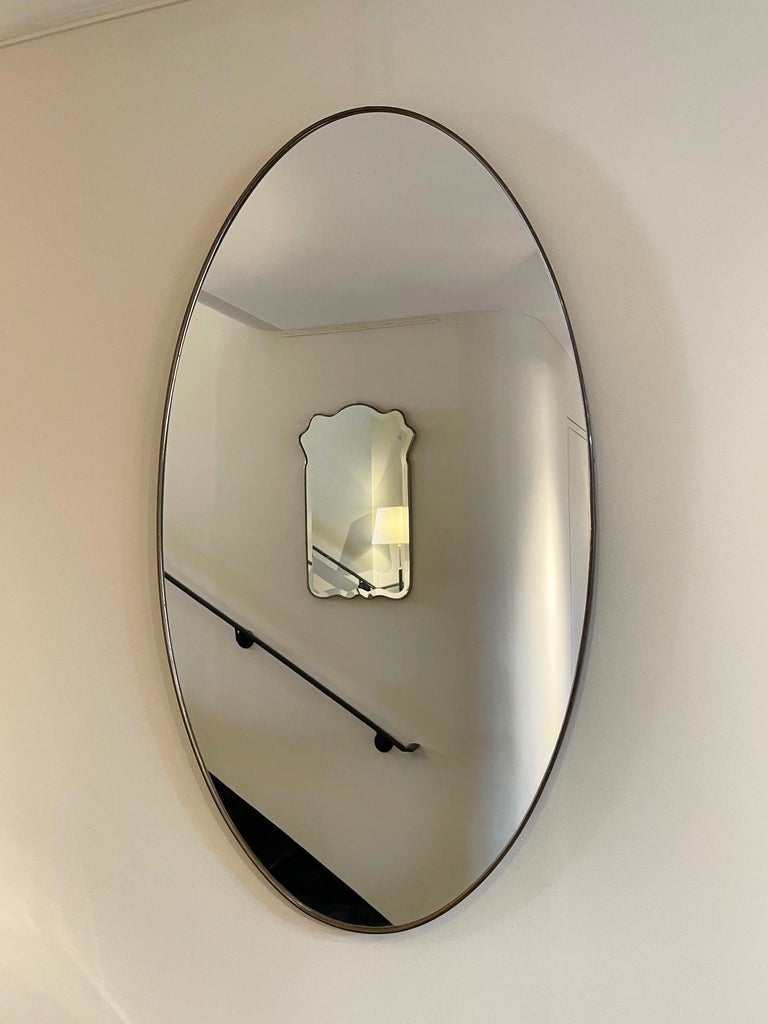 A pair of large brass framed oval mirrors. Italy, second half of the 20th century.