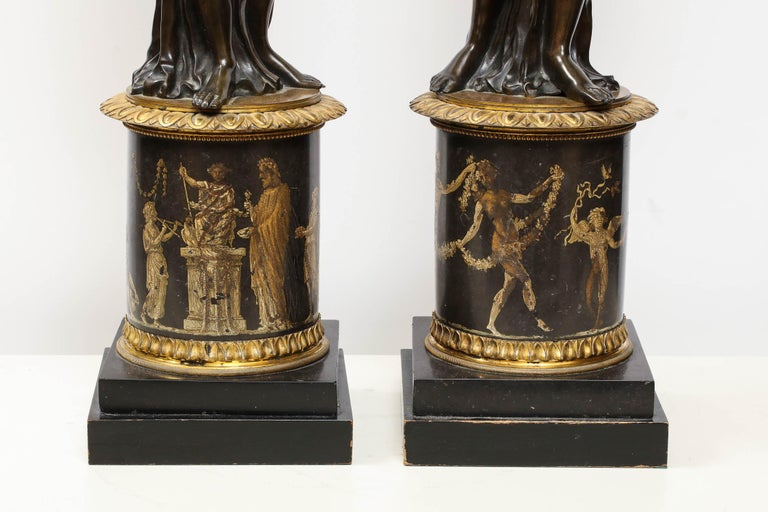 Large pair of French gilt and patinated bronze figural candleholders,  circa 1820-1830.   In the manner of Francois Remond, each modeled as a maiden holding a cornucopia above a cylindrical pedestal painted to show a continuous band of classical