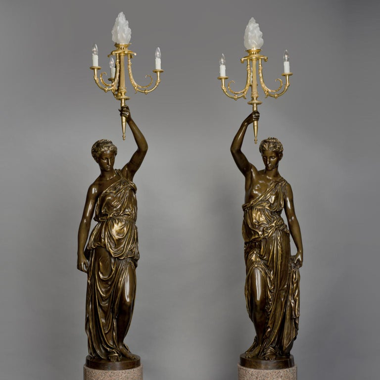 A magnificent and large pair of gilt and patinated bronze figural candelabra, Cast by Ferdinand Barbedienne after the Models by Alexandre Falguière and Paul Dubois, raised on rose granite bases. 