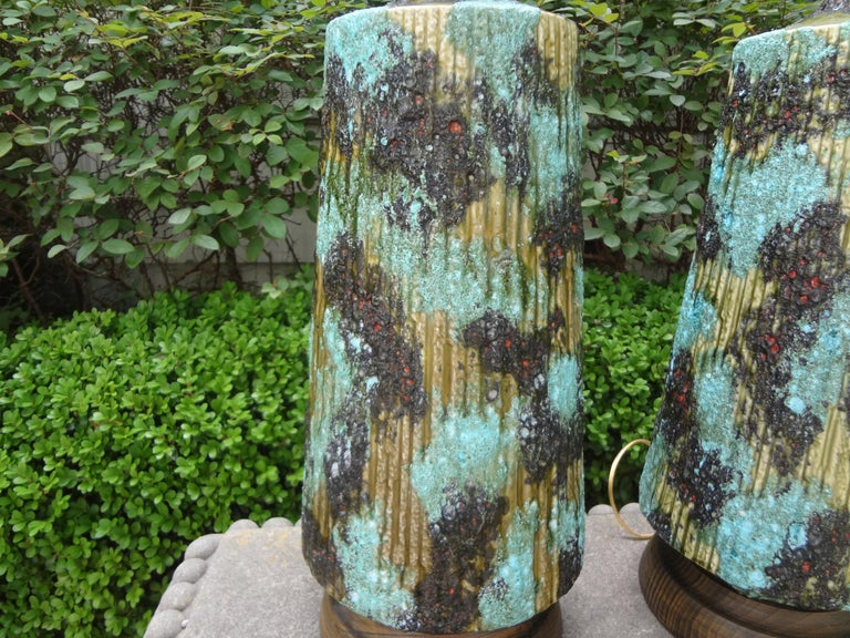 Stunning large pair of Italian glazed ceramic lamps. This unusual pair of Italian lamps are in a gorgeous shade of turquoise mounted on wood bases and newly wired to U.S. standards. These fantastic Italian Hollywood Regency lamps are attributed to