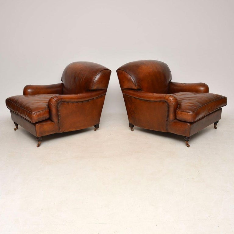 Large pair of leather antique 'Howard' style armchairs in wonderful condition and extremely comfortable. The leather is a wonderful color with loads of character and a great antique look. These armchairs are in excellent condition & I would say they