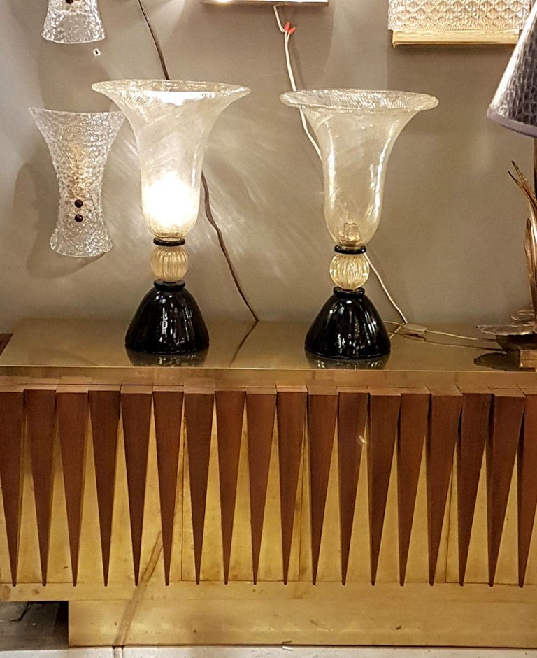 Large pair of Mid-Century Modern Murano glass urn shaped lamps, Venini style and quality. Made of a black opaque Murano glass base, and a large clear with gold inclusions top vase, containing the light, and decorated with the Rigadin Murano glass