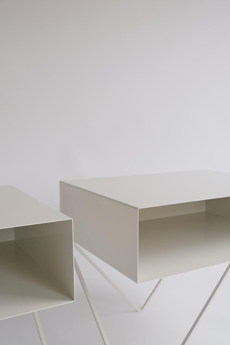 A large pair of elegant paper white powder-coated steel Robot bedside tables. The Robot side table features an open shelf on zig zag legs. A wide, low elegant design made of solid steel, powder coated in paper white. The clean lines look great